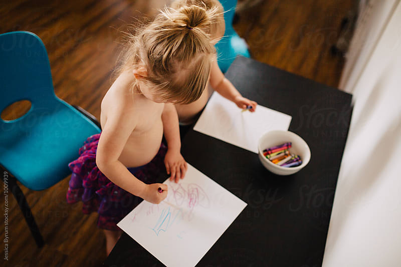 Blonde toddler siblings standing at a small table coloring with crayons. by Jessica Byrum for Stocksy United