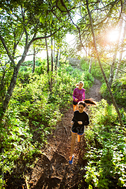 Overhead View of Two Women Running Down a Trail by Willie Dalton for Stocksy United