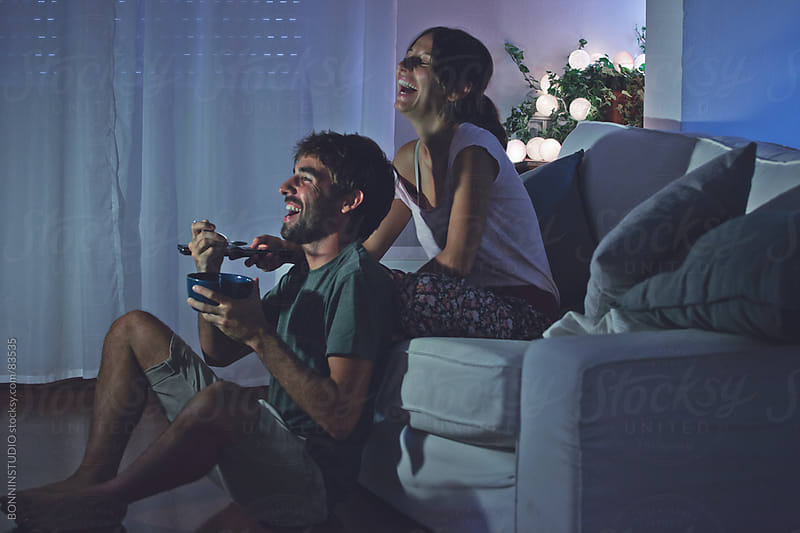 Young couple laughing watching movies at home. by BONNINSTUDIO for Stocksy United
