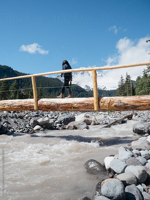 Young woman hiking on log over river with mountain in back. Washington. by Jeremy Pawlowski for Stocksy United