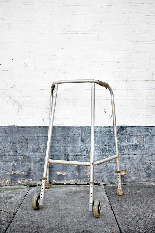 A walking frame left by a wall by James Ross for Stocksy United