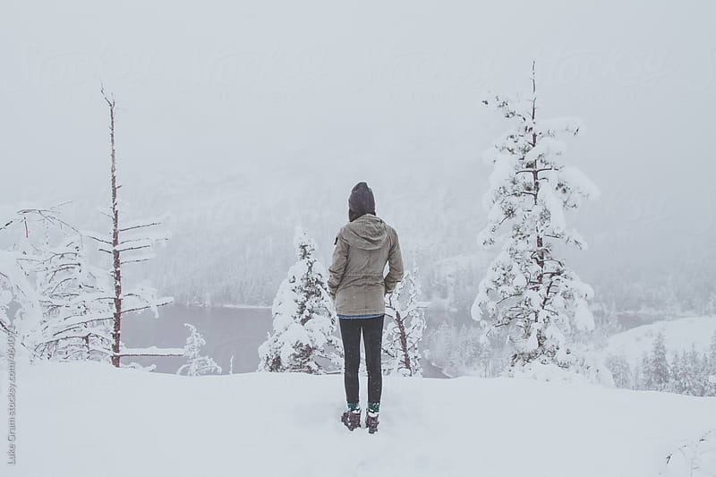 Girl hiking in the snow by a mountain lake by Luke Gram for Stocksy United