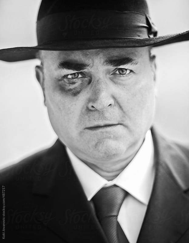 portrait of a man in a suit with black hat by Koki Jovanovic for Stocksy United