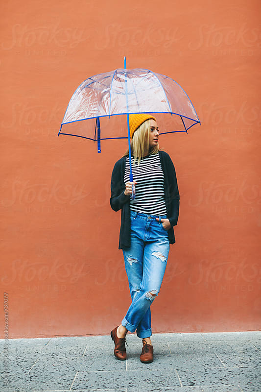 Blonde woman holding an umbrella in front of an orange wall. by BONNINSTUDIO for Stocksy United