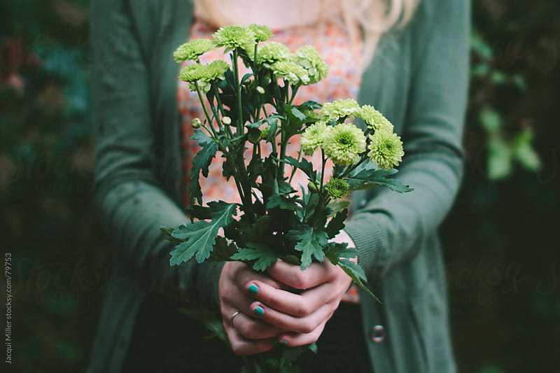 Girl holding a small bunch of green flowers by Jacqui Miller for Stocksy United