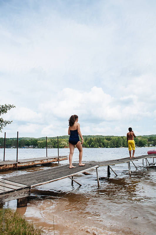 two children walk along a dock by Margaret Vincent for Stocksy United