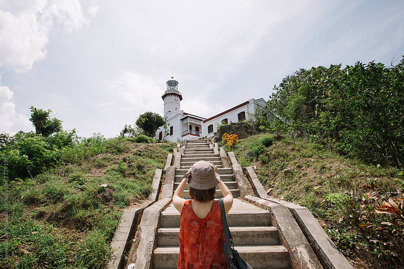 A lady tourist takes a souvenir photo of a lighthouse built during the Spanish colonial period  by Lawrence del Mundo for Stocksy United