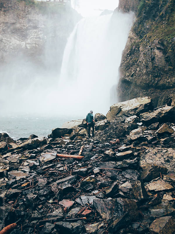Man Walks On Rocks In Front Of Roaring Waterfall by Luke Mattson for Stocksy United