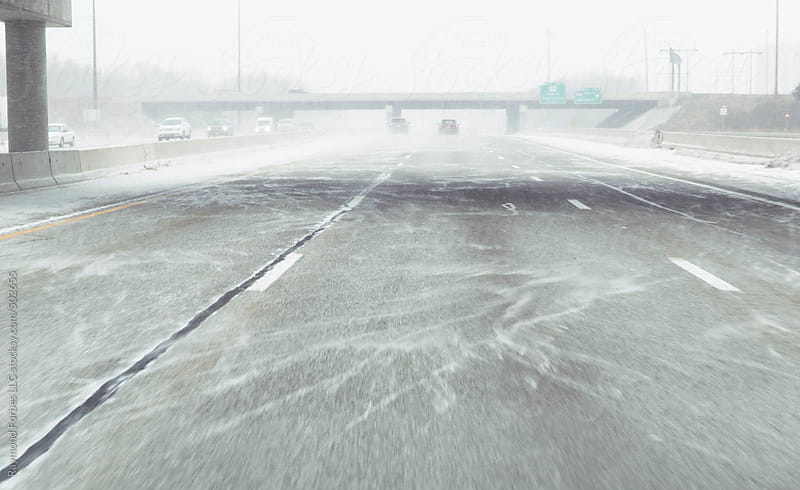 Driving down Highway in Snowstorm by Raymond Forbes LLC for Stocksy United