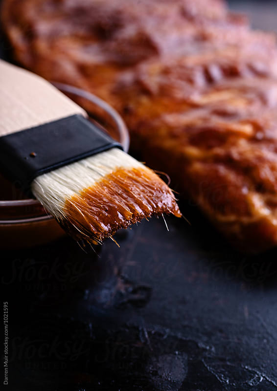 A brush with barbecue sauce used for rubbing the mix onto a rack of ribs. by Darren Muir for Stocksy United