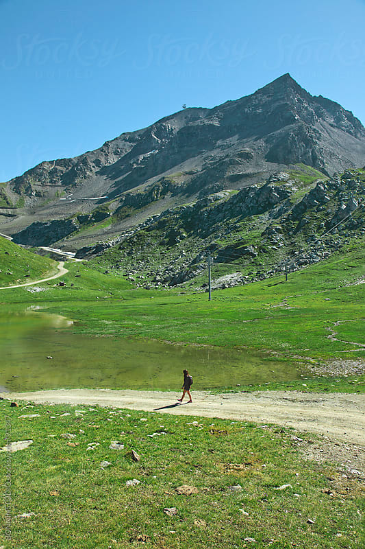 Hiker woman walking on  beautiful natural road. Alps, france. by BONNINSTUDIO for Stocksy United