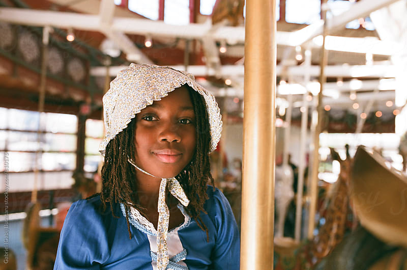 African American girl in old-fashioned dress on a carousel by Gabriel (Gabi) Bucataru for Stocksy United
