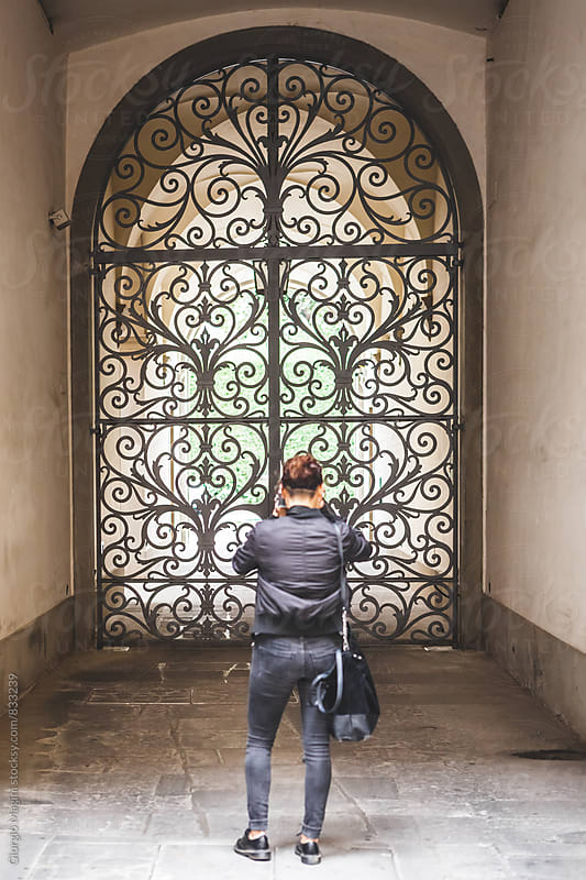 Young Woman Photographing an Iron Gate in Italy by Giorgio Magini for Stocksy United