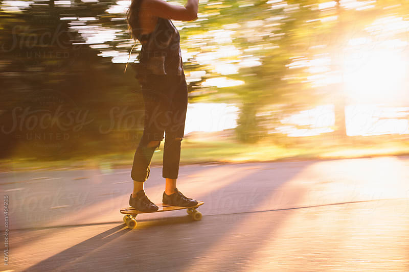 Wild young girl skateboards down the street on a fall day by HOWL for Stocksy United