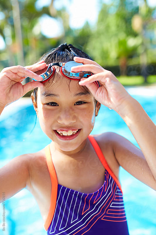 close up of one happy asian little girl in swimming pool by Bo Bo for Stocksy United
