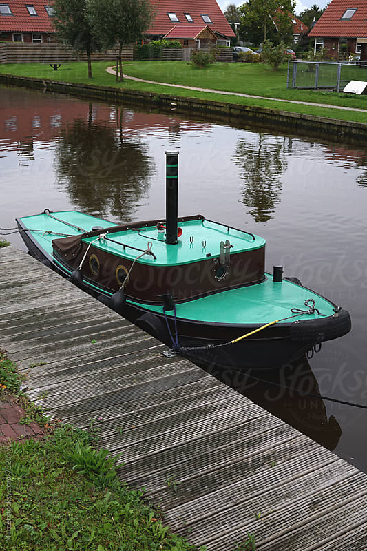 Cute little boat in a  dutch canal by Marcel for Stocksy United
