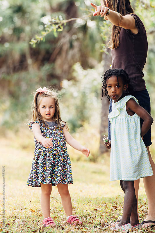 Caucasian and African American girls with their mother on a nature walk by Gabriel (Gabi) Bucataru for Stocksy United
