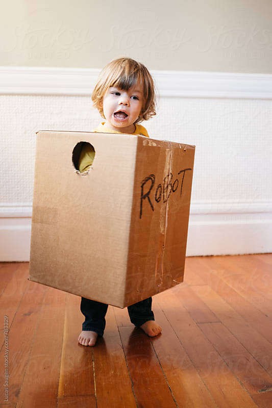 Boy stands in a homemade robot costume. by Lucas Saugen for Stocksy United