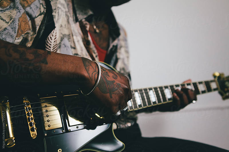 Close up of tattooed hands playing guitar by kkgas for Stocksy United