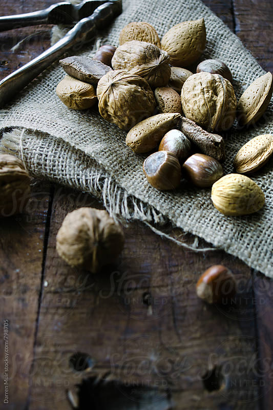 Mixed shell nuts on a piece of burlap on a wooden background. by Darren Muir for Stocksy United
