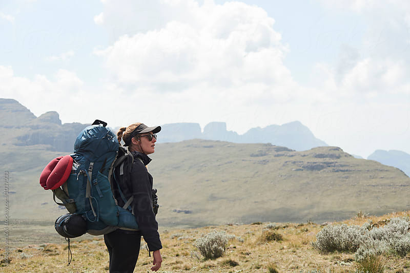 Female hiker with her back pack in the mountains  by Jacques van Zyl for Stocksy United