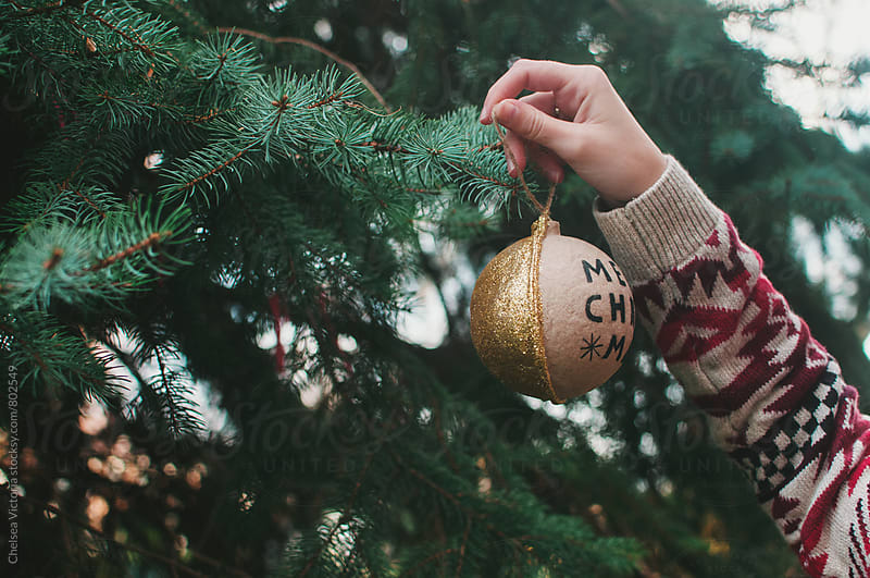 A young woman places a christmas ornament on a tree by Chelsea Victoria for Stocksy United