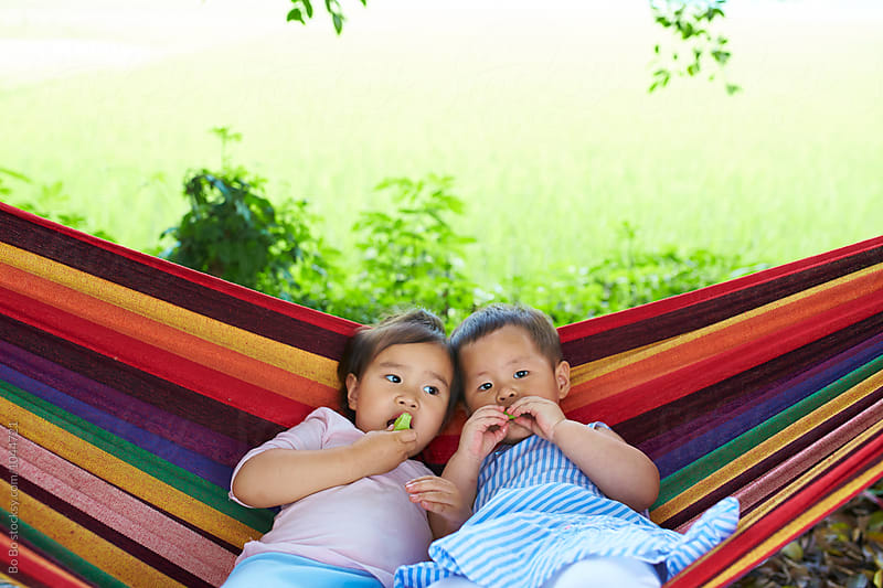 two little girs eating fruit in hammock outdoor by Bo Bo for Stocksy United