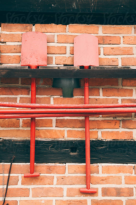 Pair of red shovels on brick wall. by Marija Savic for Stocksy United