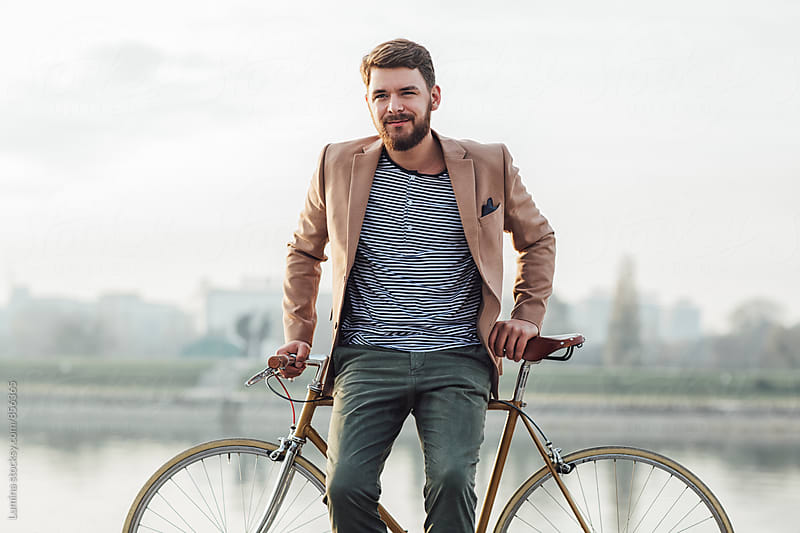 Businessman on a Bicycle by the River. by Lumina for Stocksy United
