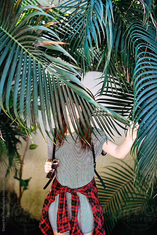 Woman covering face with palm frond by Daniel Kim Photography for Stocksy United