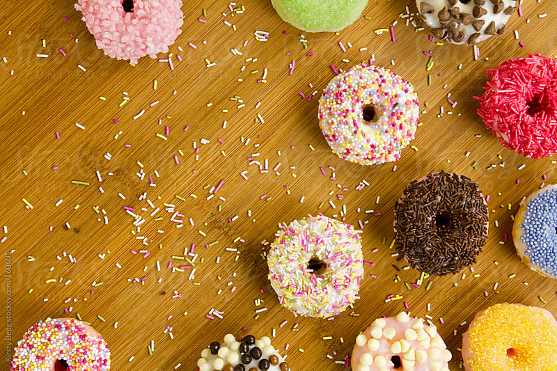 Iced doughnuts on board with copy space by Kirsty Begg for Stocksy United