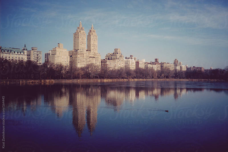 Film photo of Central Park, New York City, with its lake and surrounded buildings by Kaat Zoetekouw for Stocksy United
