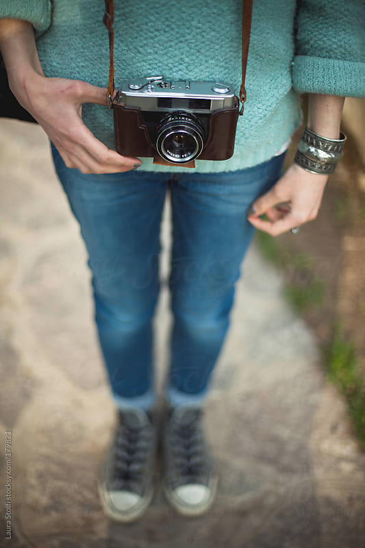 Detail of old analogical camera in leather bag hanging from girl's neck by Laura Stolfi for Stocksy United