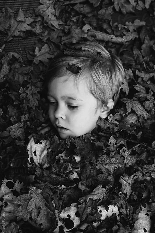 Black and white of little girl with eyes closed covered in leaves. by Julia Forsman for Stocksy United