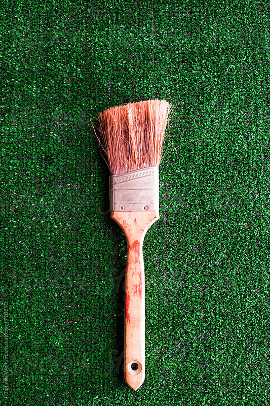 A used and worn paintbrush laying on artificial grass. by J Danielle Wehunt for Stocksy United