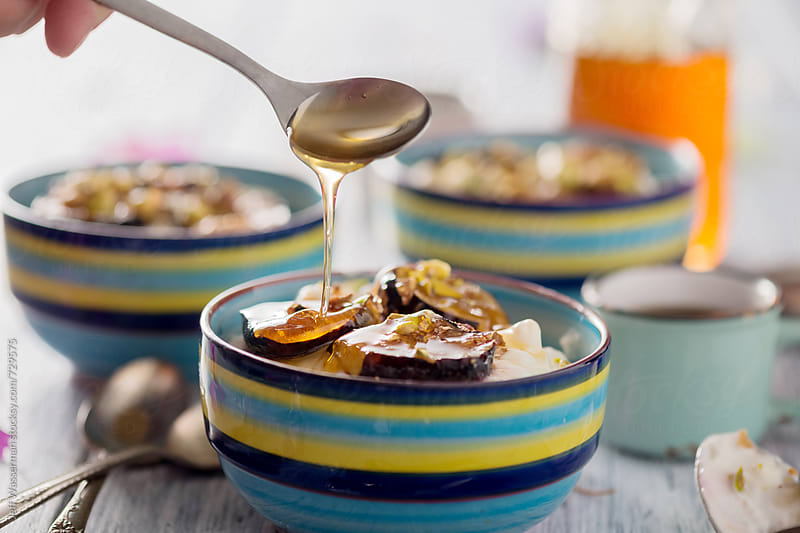 Dirzzling Honey on Yogurt with Roasted Figs by Jeff Wasserman for Stocksy United