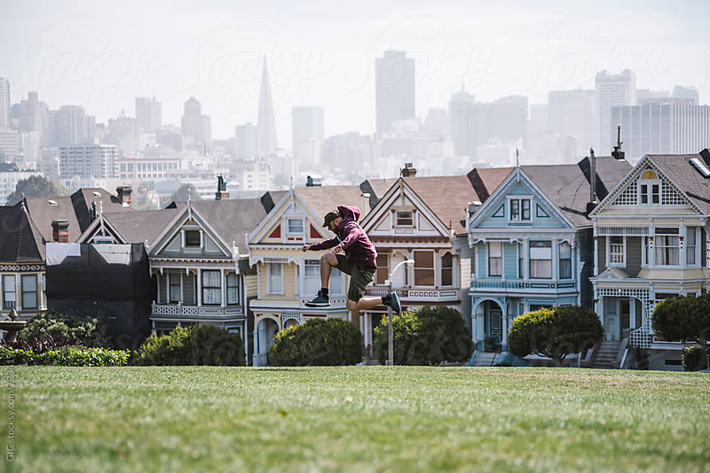 Man jumping against San Francisco skyline by Simone Becchetti for Stocksy United