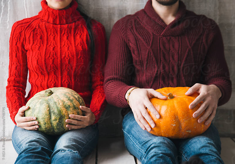 Couple holding pumpkins by T-REX & Flower for Stocksy United