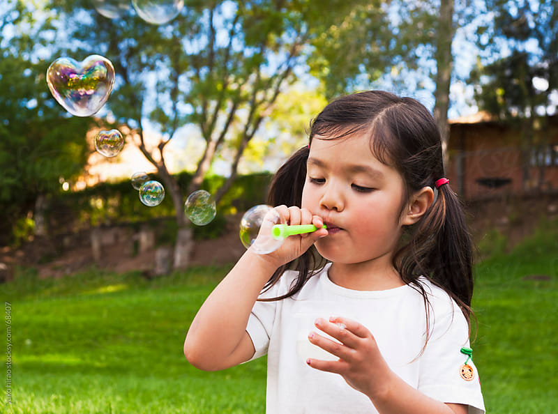Little girl, blowing heart bubbles by yuko hirao for Stocksy United