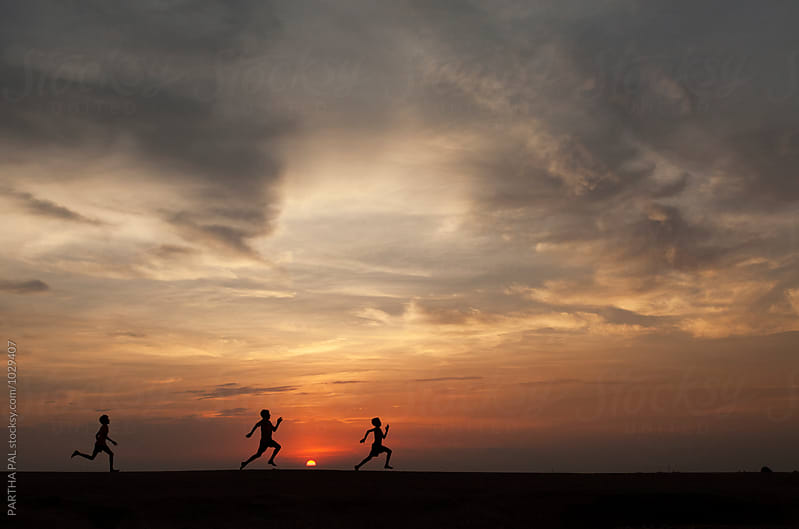Three rural boys running a rache through wonderful landscape by PARTHA PAL for Stocksy United