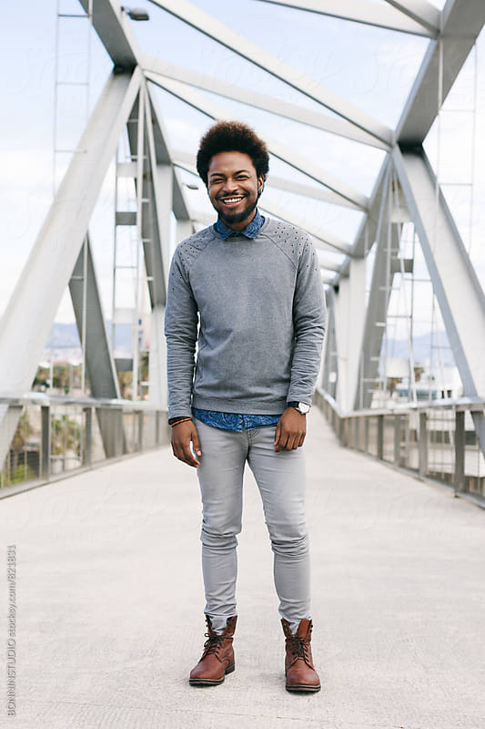 Portrait of an african american man standing on a modern bridge. by BONNINSTUDIO for Stocksy United