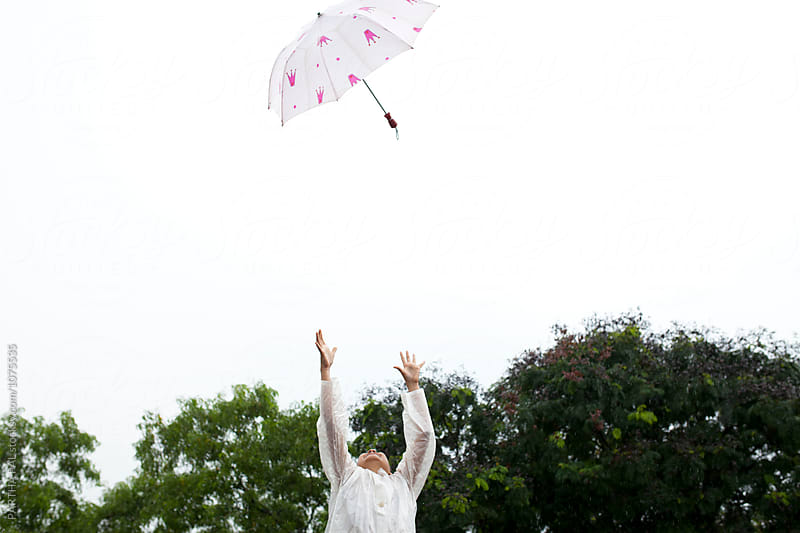 A girl throwing umbrella in air by PARTHA PAL for Stocksy United