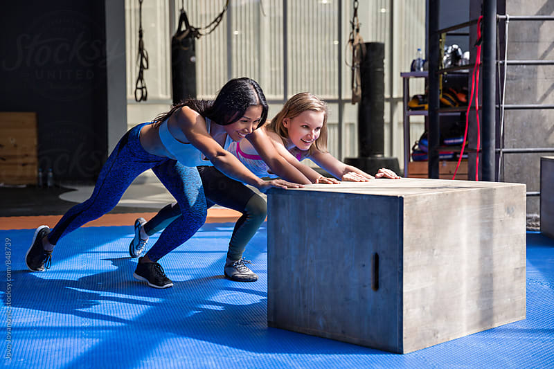 Two workout friends pushing a plyo box by Jovo Jovanovic for Stocksy United