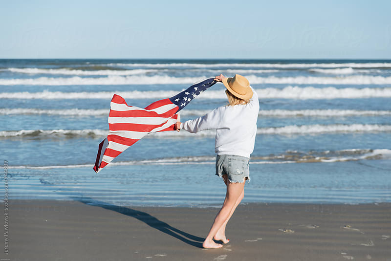 Woman running with American Flag on the beach. 4th of July at the ocean. by Jeremy Pawlowski for Stocksy United