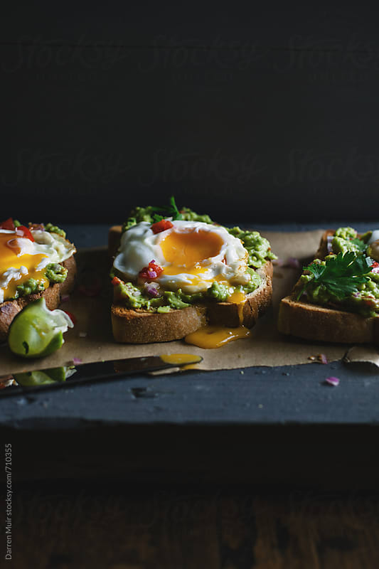 Avocado and fried egg toasts on a table. by Darren Muir for Stocksy United