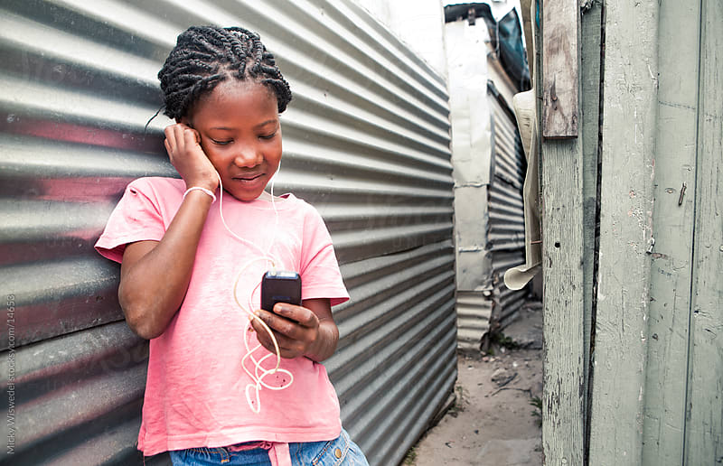 Cute African girl listening to music by Micky Wiswedel for Stocksy United