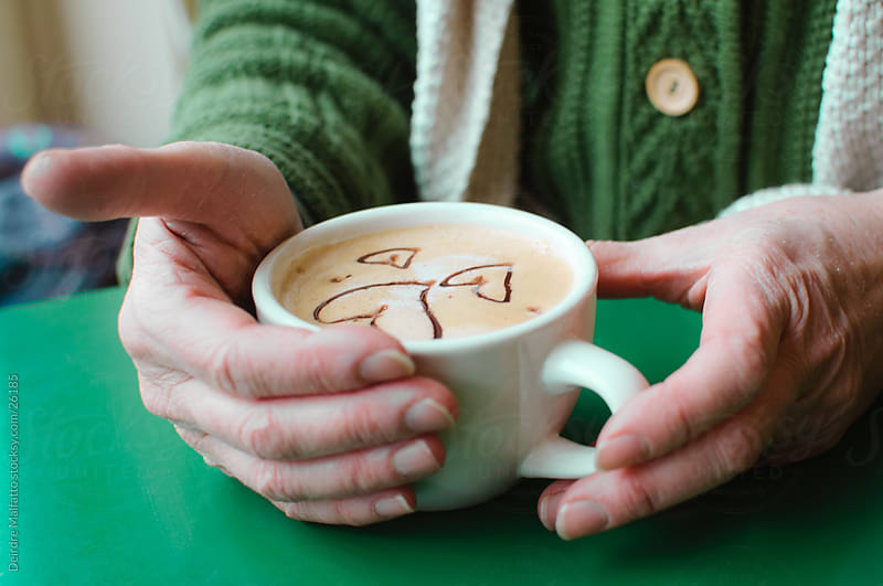 Hands holding a latte that is decorated with hearts by Deirdre Malfatto for Stocksy United