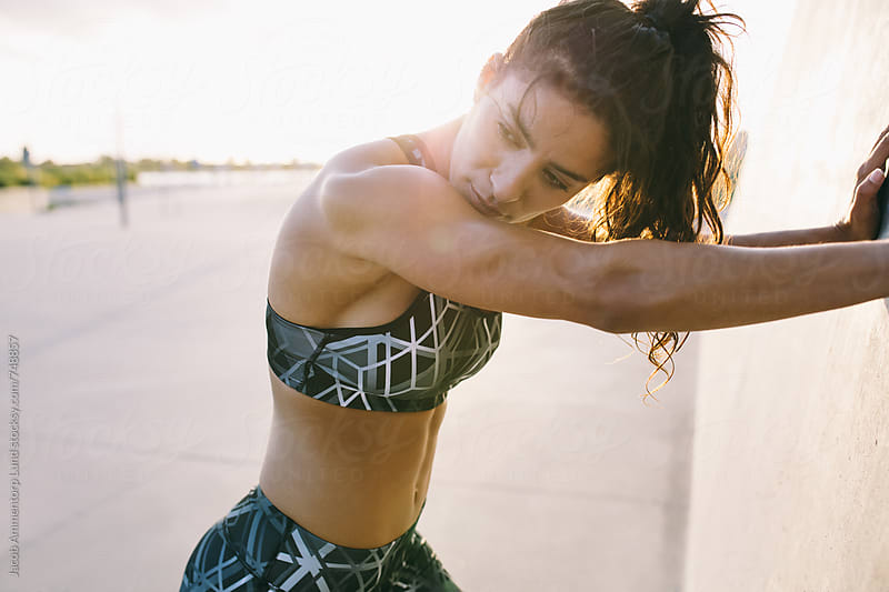Portrait of woman stretching after workout by Jacob Lund for Stocksy United