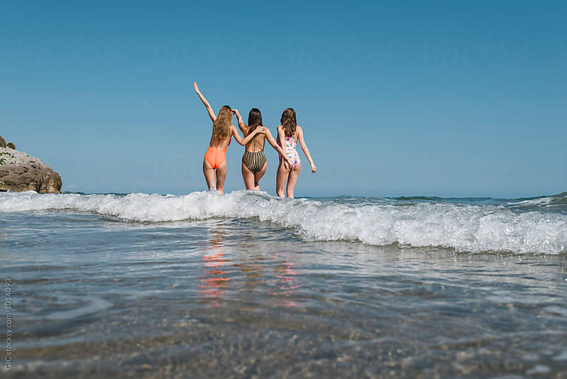 Three girls having fun in the sea by Simone Becchetti for Stocksy United