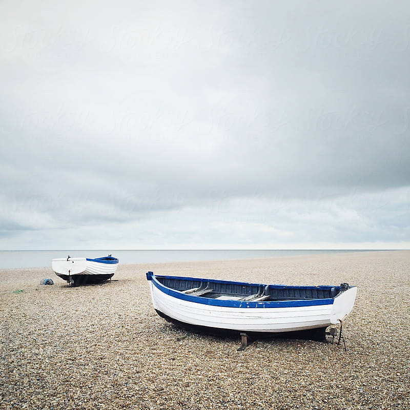 Two wooden boats on a beach by James Ross for Stocksy United